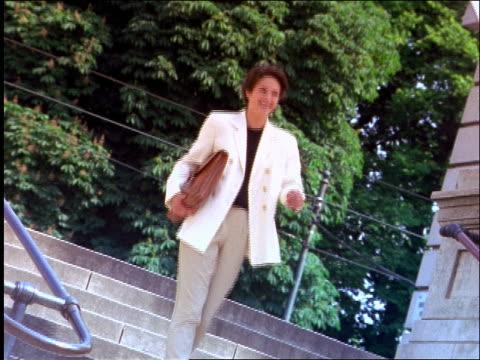 vídeos de stock e filmes b-roll de businesswoman carrying briefcase smiling + walking down steps outdoors - trabalhadora de colarinho branco