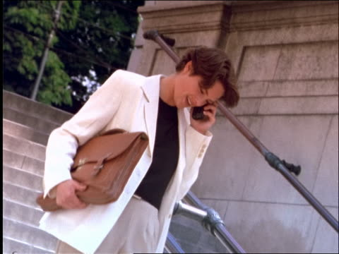 businesswoman carrying briefcase walking down steps + talking + laughing on cellular phone outdoors - 1997 stock-videos und b-roll-filmmaterial