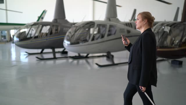 businesswoman carrying luggage and using smartphone in a hangar - side view stock videos & royalty-free footage