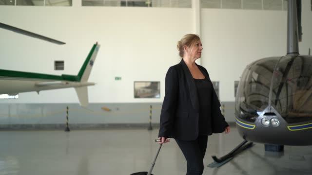vídeos y material grabado en eventos de stock de mujer de negocios llevando equipaje en un hangar - encuadre de tres cuartos