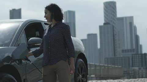 vídeos y material grabado en eventos de stock de businesswoman charging electric car at charging station in city, with skyline - coche eléctrico coche alternativo