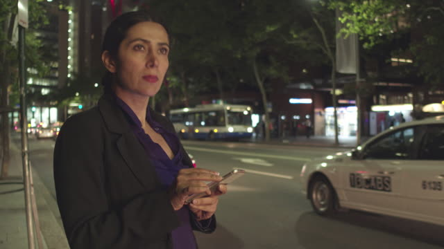 businesswoman checking mobile app as waiting for taxi in the night - nightlife stock videos & royalty-free footage