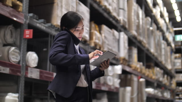 businesswoman checking order stock using digital tablet in distribution warehouse - stationary stock videos & royalty-free footage