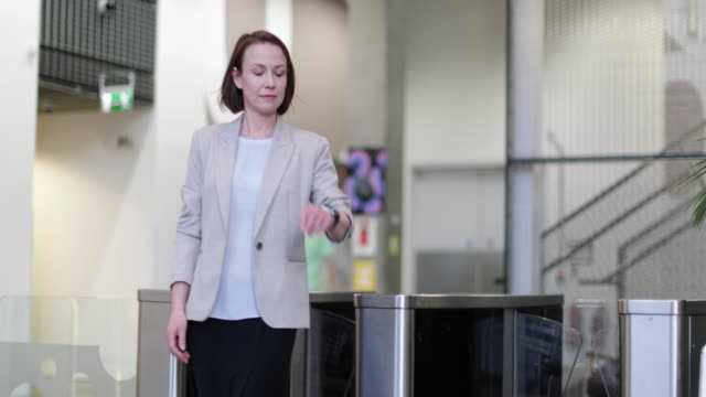 businesswoman checking smartwatch as leaving office - building entrance stock videos and b-roll footage