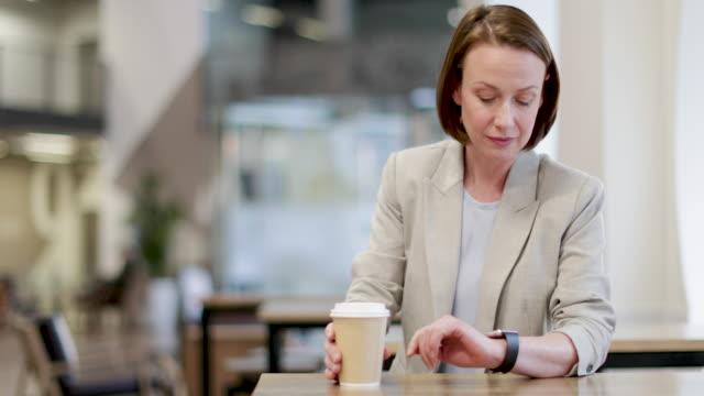 businesswoman checking smartwatch in cafe - gedächtnisstütze stock-videos und b-roll-filmmaterial