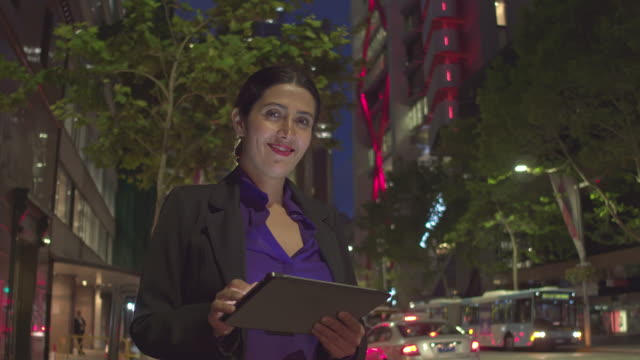 Businesswoman checking the digital tablet in the street at night