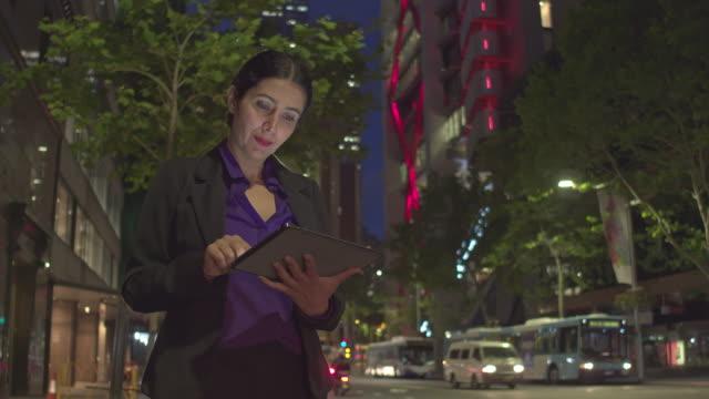 stockvideo's en b-roll-footage met zakenvrouw controleren van de digitale tablet in de straat in de nacht - driekwartlengte
