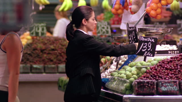 Businesswoman choosing fruit in grocery store/market / people pass in foreground / Barcelona, Spain