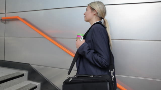 Businesswoman climbing stairs in train station