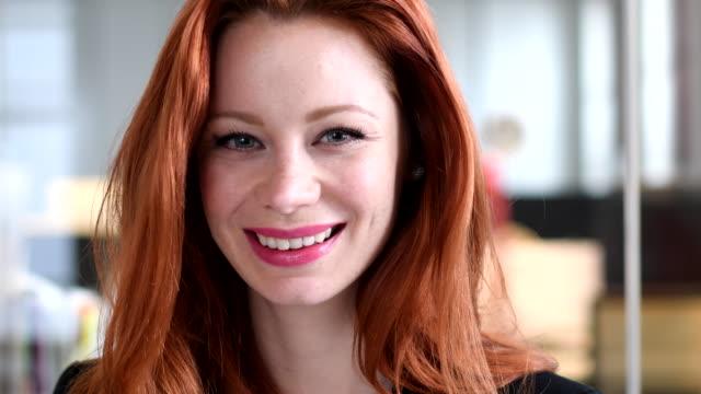 Geschäftsfrau Nahaufnahme Portrait auf der Suche nach unten und dann in die Kamera Lächeln