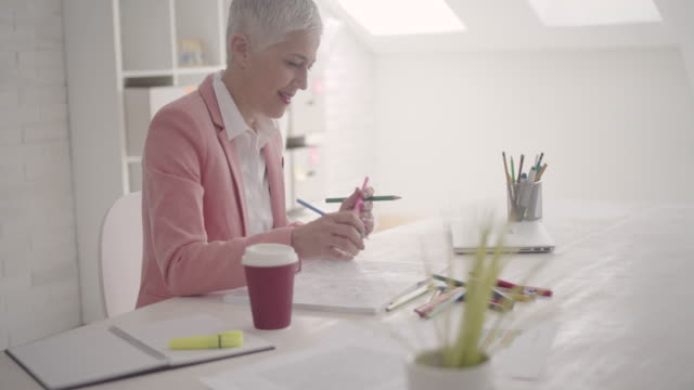 businesswoman coloring book in her office - short hair stock videos & royalty-free footage