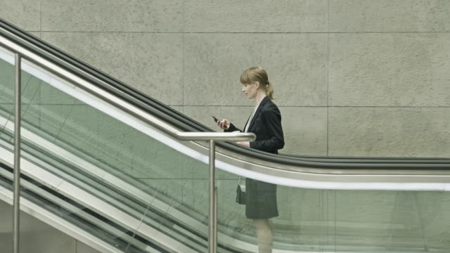 businesswoman commuting in train stairs with phone - railings stock videos & royalty-free footage