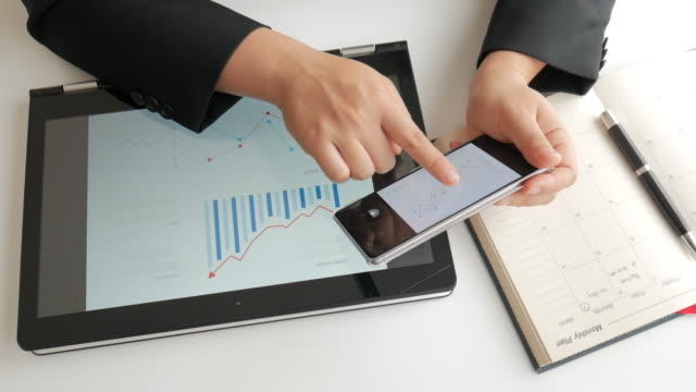 Businesswoman comparison data on smartphone and digital tablet