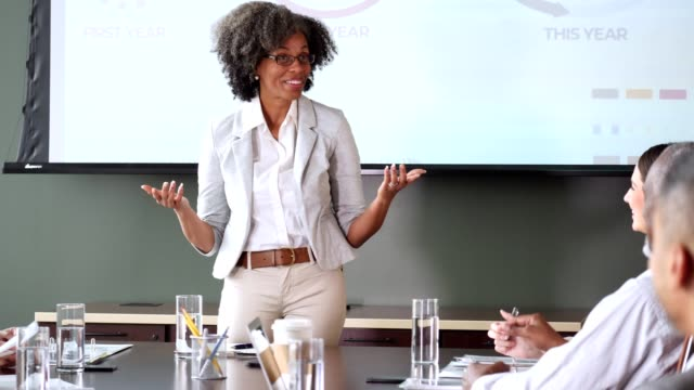 businesswoman confidently gives presentation during meeting - giving stock videos & royalty-free footage