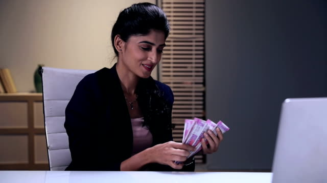 Businesswoman counting indian two thousand banknotes, Delhi, India