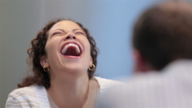 businesswoman cracks up in office conference-room meeting - ridere video stock e b–roll