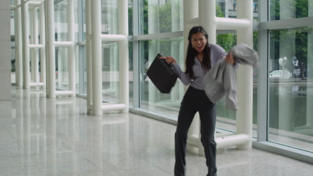 MS Businesswoman dancing in office lobby, Bangkok, Thailand