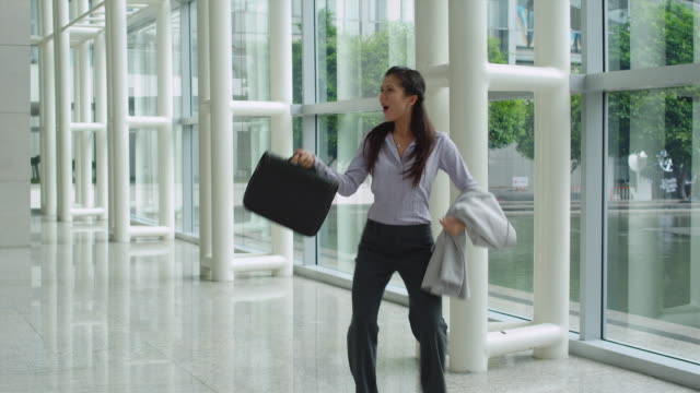 vidéos et rushes de ms businesswoman dancing in office lobby, bangkok, thailand - jetée
