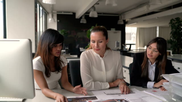 Businesswoman discussing project with coworkers