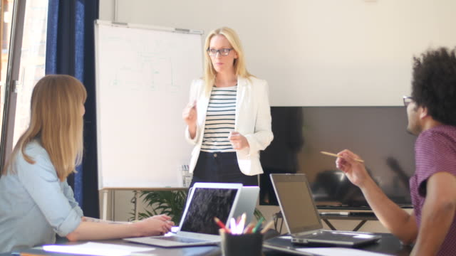 businesswoman discussing strategy with colleagues - flow chart stock videos & royalty-free footage