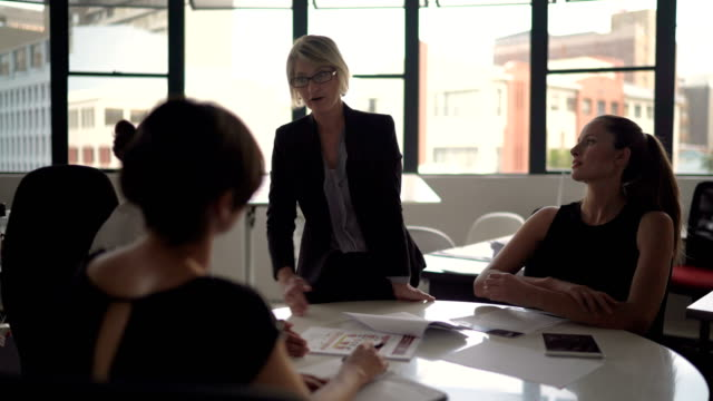 businesswoman discussing with colleagues at table - round table discussion stock videos & royalty-free footage