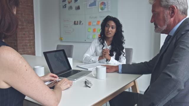 vídeos de stock, filmes e b-roll de mulher de negócios a discutir com seus colegas de trabalho em escritório - inglaterra