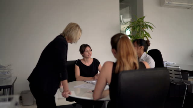 businesswoman discussing with coworkers at table - round table discussion stock videos & royalty-free footage