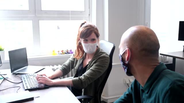 geschäftsfrau diskutiert arbeit durch glastrennwand mit kollegin - arbeitssicherheit stock-videos und b-roll-filmmaterial