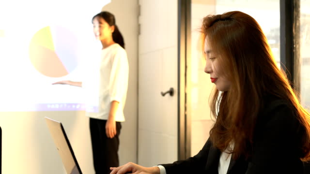 A businesswoman doing a presentation and a woman typing on a keyboard