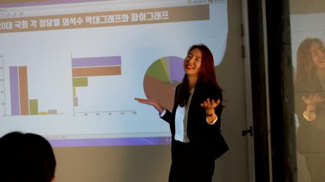 a businesswoman doing a presentation at a seminar - liniendiagramm stock-videos und b-roll-filmmaterial
