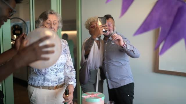 Femme d'affaires faisant un chat vidéo à la fête d'anniversaire dans le bureau