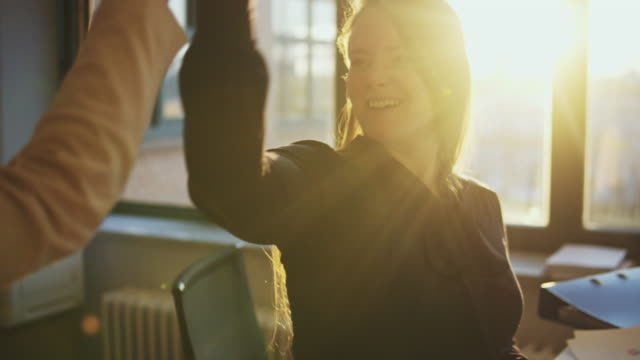 businesswoman doing high-five in office. - high five stock-videos und b-roll-filmmaterial