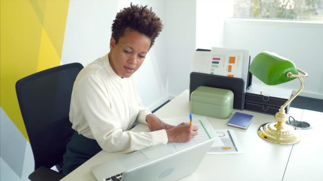 businesswoman doing paperwork. - documento video stock e b–roll