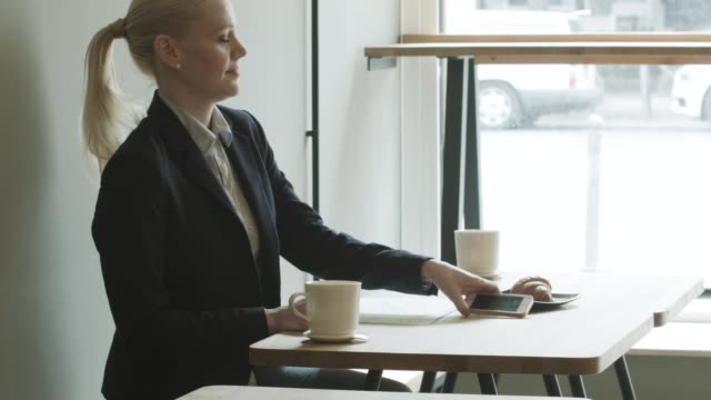 businesswoman drinking coffee in cafe - haar nach hinten stock-videos und b-roll-filmmaterial