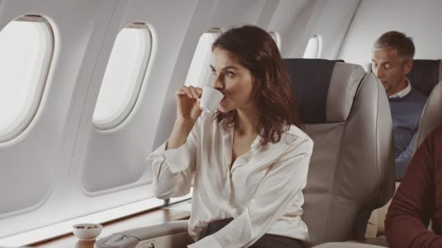 geschäftsfrau trinkt kaffee im geschäftsjet - getränk stock-videos und b-roll-filmmaterial