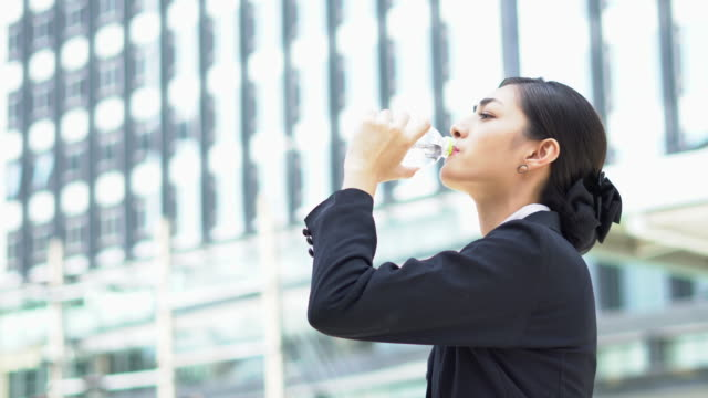 Businesswoman drinking water in the big capital city