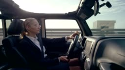 Businesswoman driving SUV. Escaping to exotic scenery