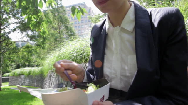 businesswoman eating lunch in city park - western european culture stock videos & royalty-free footage