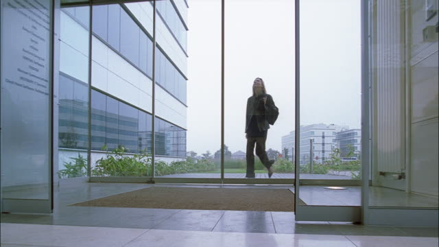 a businesswoman enters the lobby of an office building. - entering stock videos & royalty-free footage