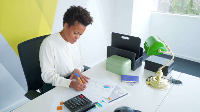 businesswoman examining documents at desk. - small office stock videos and b-roll footage