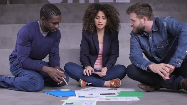 ドキュメントを同僚に説明する実業家 - 床に座る点の映像素材/bロール