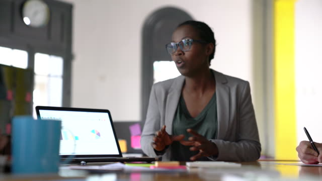Businesswoman explaining graphs through laptop