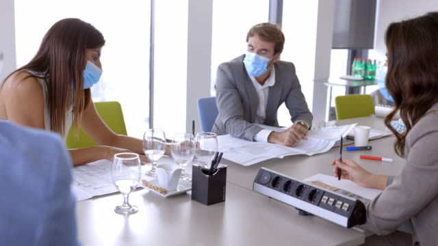 businesswoman explaining ideas to coworkers at the conference table, all wearing protective face masks - conference table stock videos & royalty-free footage