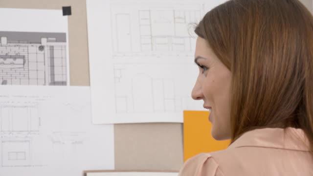 vidéos et rushes de femme d'affaires expliquant le projet avec le client - graphisme