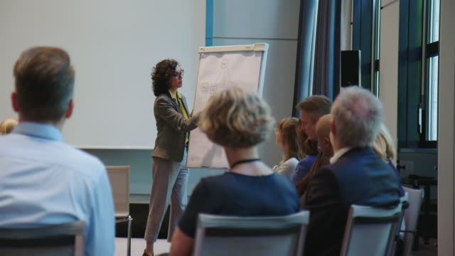 businesswoman explaining strategy over flipchart - auditorium stock videos & royalty-free footage