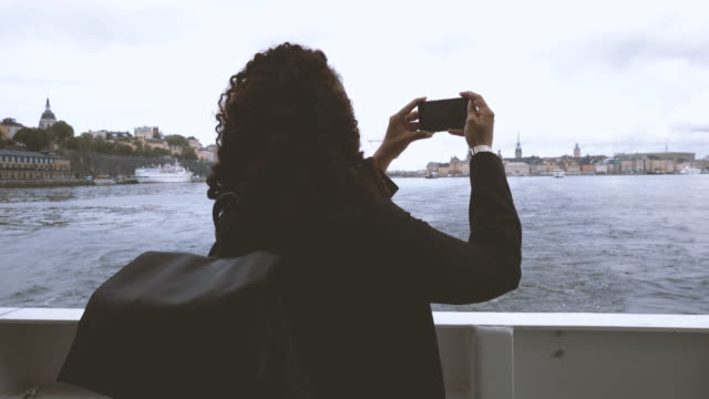 businesswoman filming with mobile phone from boat deck - stockholm stock-videos und b-roll-filmmaterial