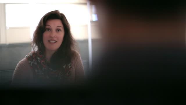 Businesswoman gestures, addresses boss in corporate office meeting; employee crosses in background