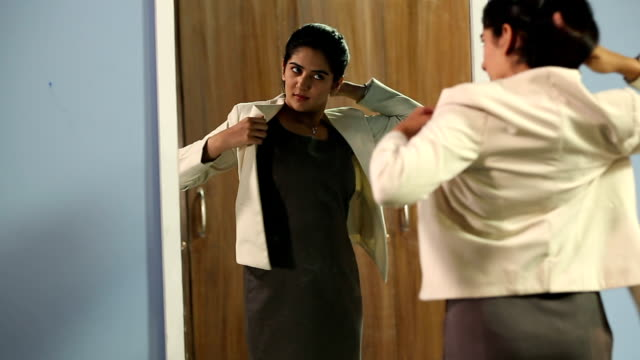 businesswoman getting dressed in front of mirror, delhi, india - coat garment stock videos & royalty-free footage