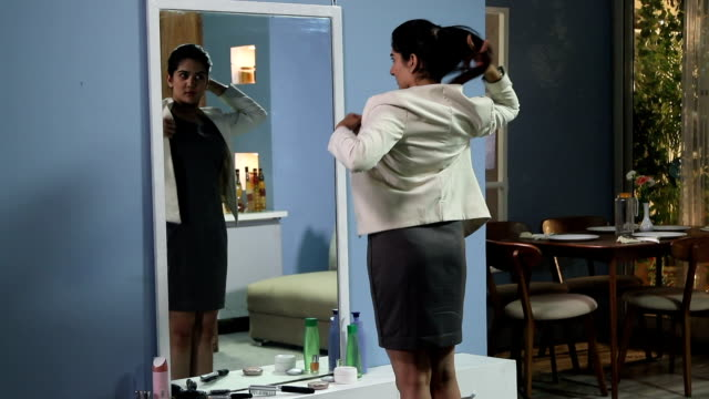 Businesswoman getting dressed in front of mirror, Delhi, India