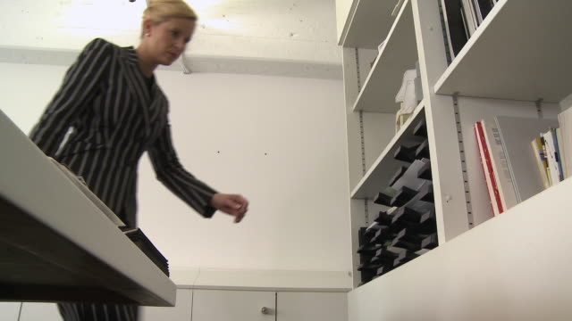 LA MS Businesswoman getting file from shelf in office / Berlin, Germany